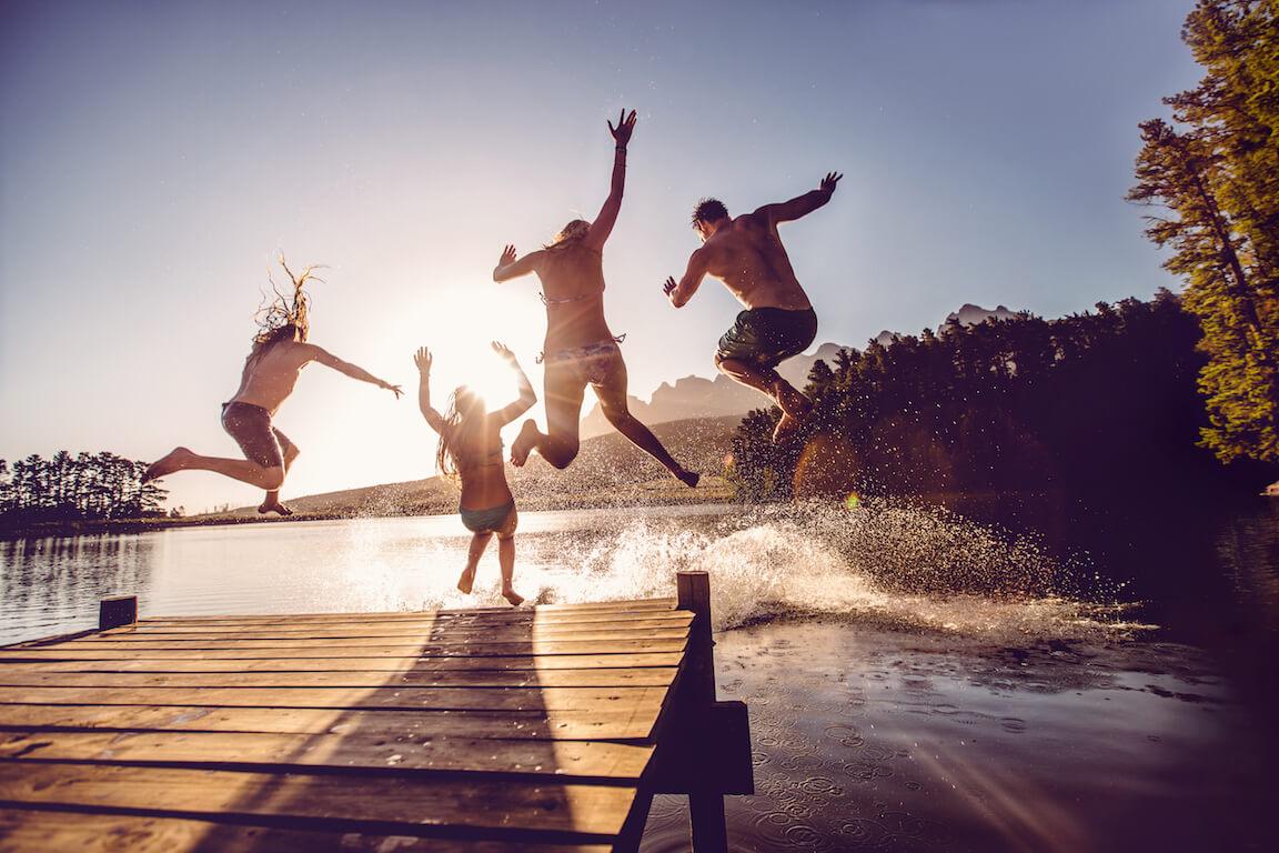 Jeunes adultes sautant dans un lac sur le bord d'un quai