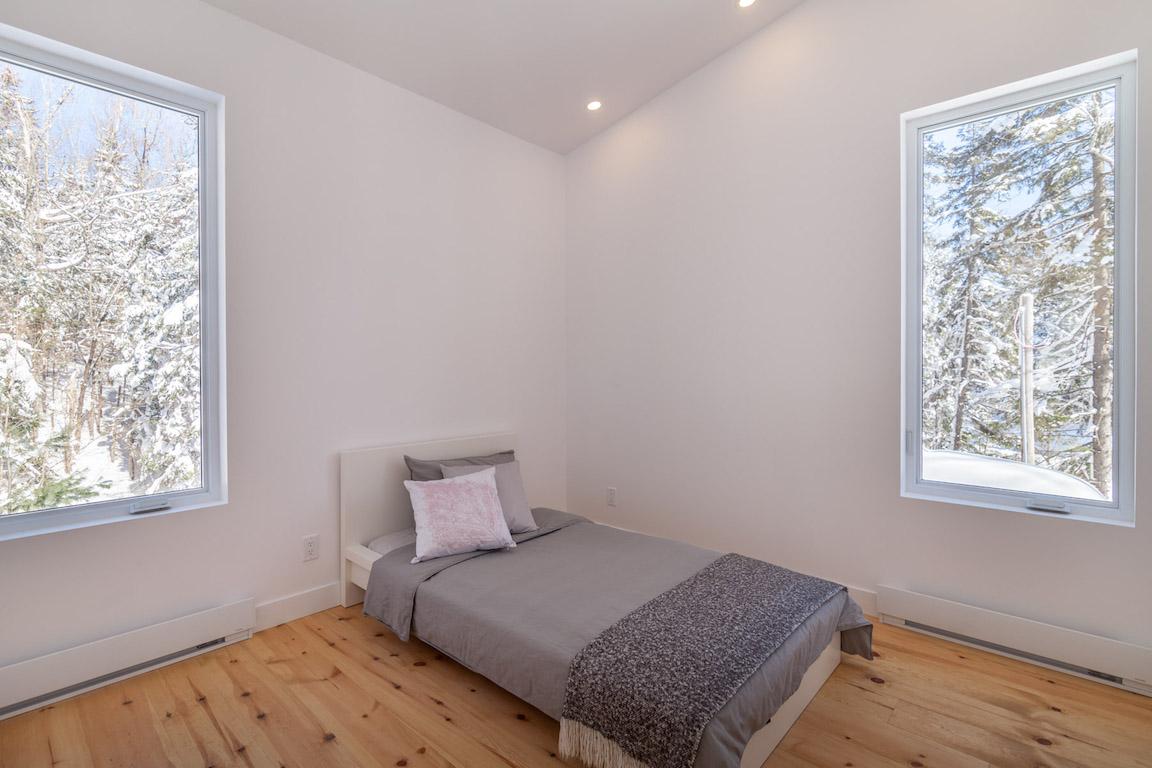 Vue d'une chambre à l'étage avec plafond cathédrale, projet La Mésange réalisé par Biophile