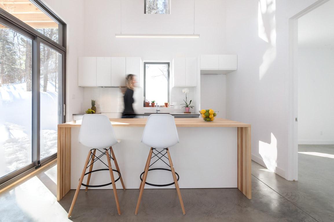 Vue de la cuisine avec fenestration abondante, projet La Mésange réalisé par Biophile