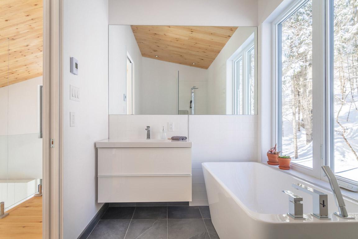 Vue de la salle de bain avec bain autoportant et douche à l'étage, projet La Mésange réalisé par Biophile