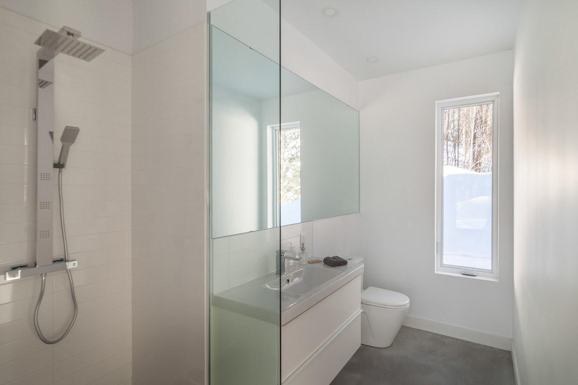 Vue de la salle de toilette avec douche au rez-de-chaussée, projet La Mésange réalisé par Biophile