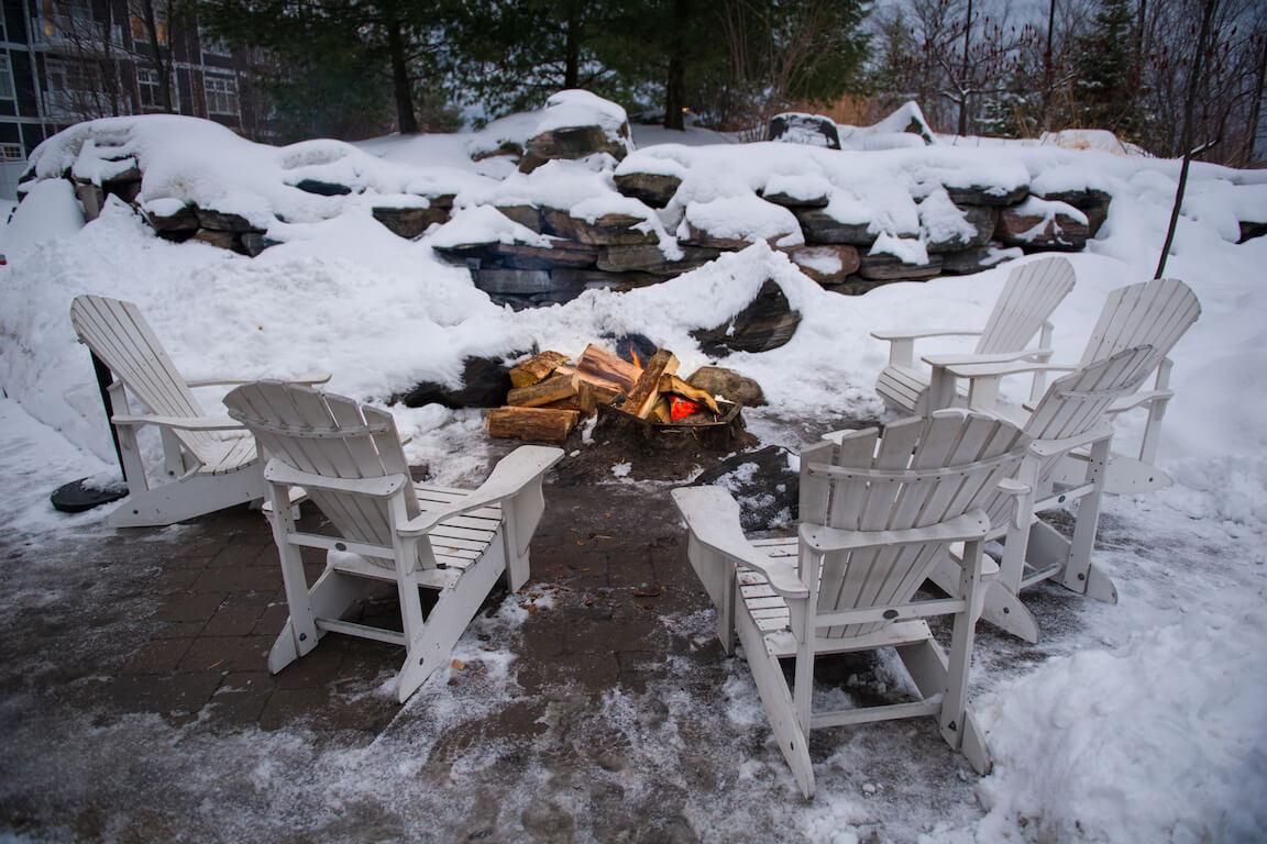 Feu extérieur rempli de bûches entouré de chaises Adirondack blanches