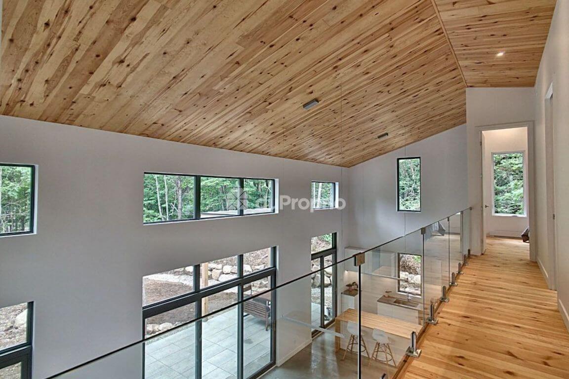 Vue du corridor à l'étage avec sa rampe en verre et son plafond cathédrale, projet La Mésange réalisé par Biophile