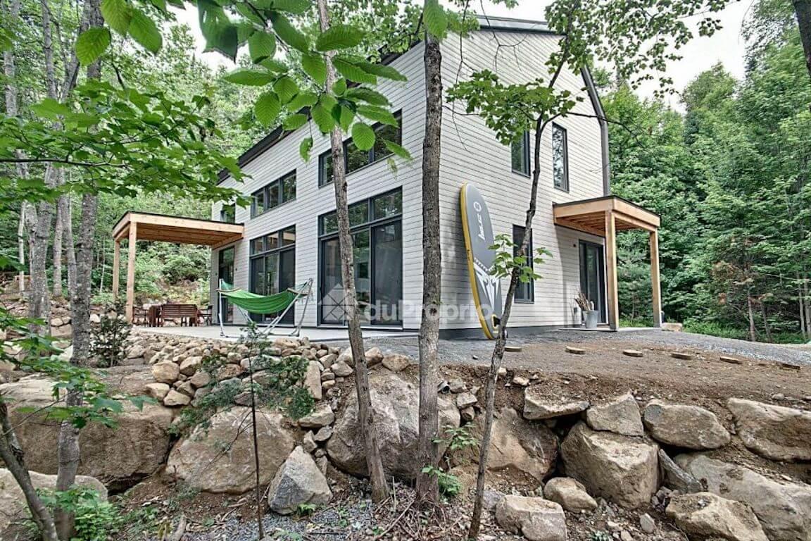 Vue de la maison avec sa grande terrasse extérieure côté sud, projet La Mésange réalisé par Biophile