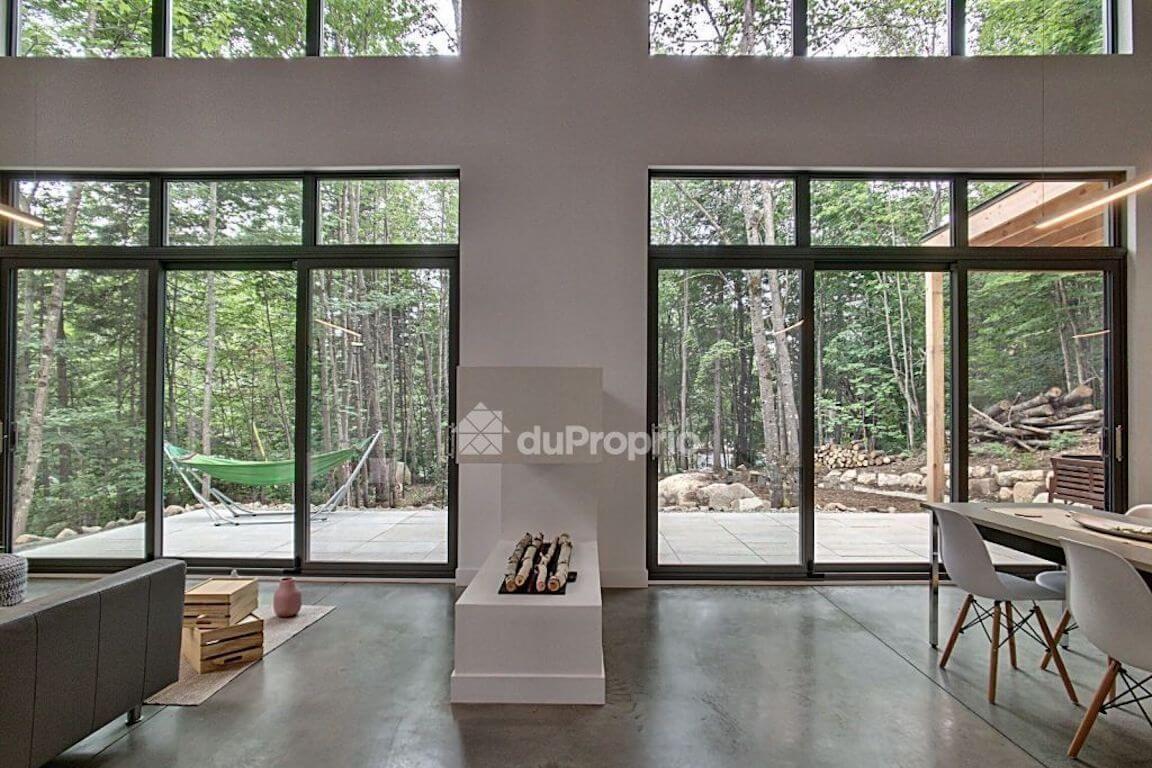 Vue de l'aire ouverte au rez-de-chaussée avec foyer 3 faces et fenestration abondante, projet La Mésange réalisé par Biophile