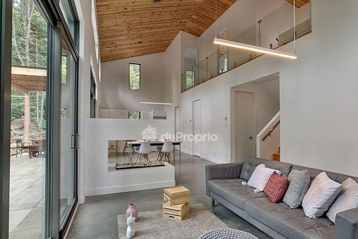 Vue du salon à aire ouverte avec foyer, projet La Mésange réalisé par Biophile