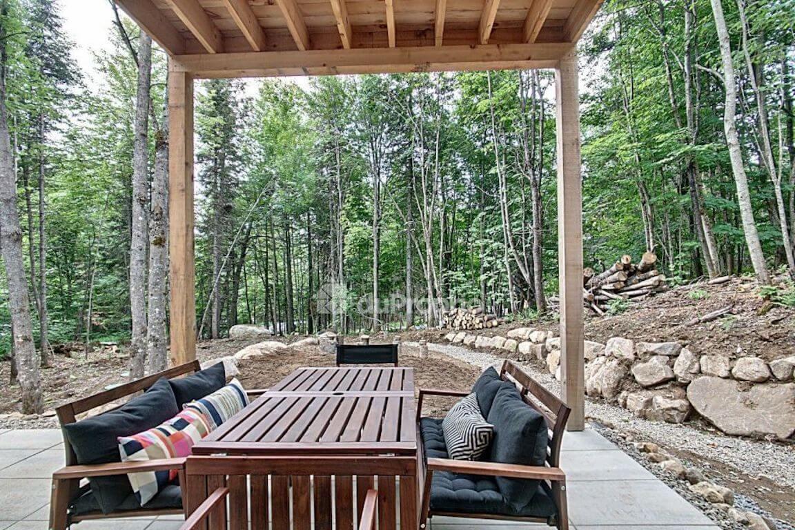 Vue partielle de la terrasse et de la forêt environnante, projet La Mésange réalisé par Biophile