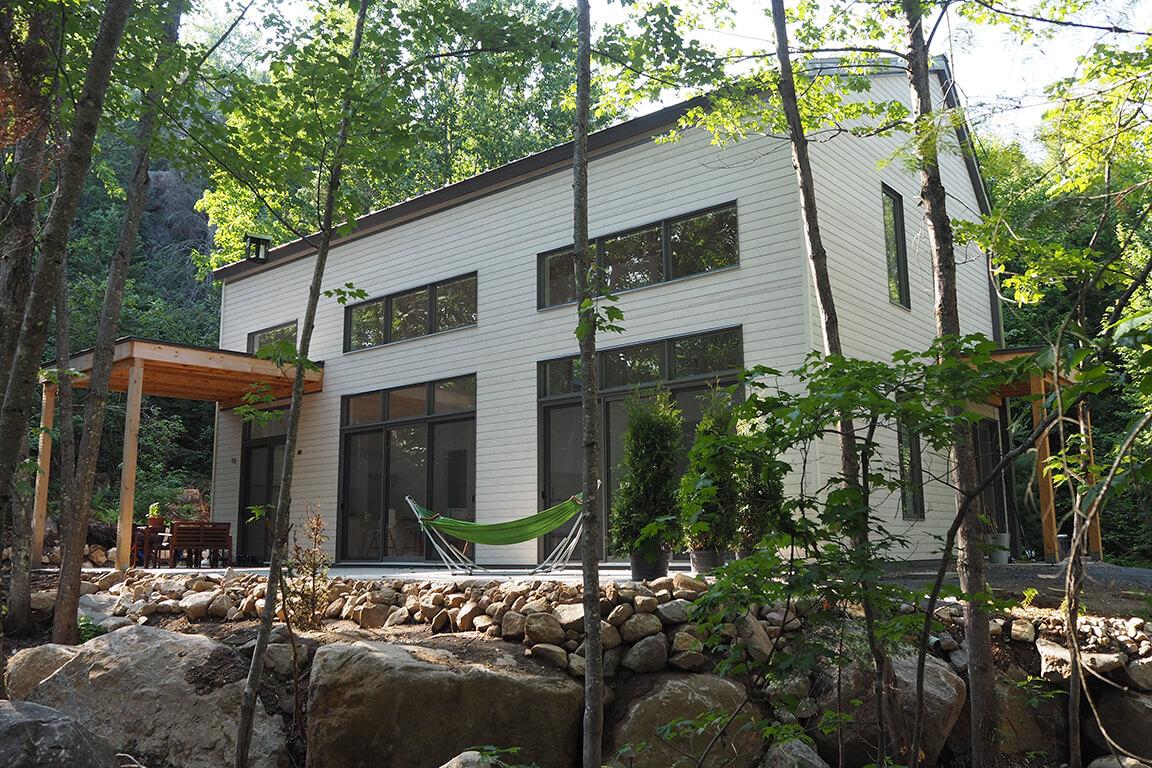 Vue de la façade sud avec sa grande terrasse et sa fenestration abondante dans un environnement boisé, projet La Mésange réalisé par Biophile