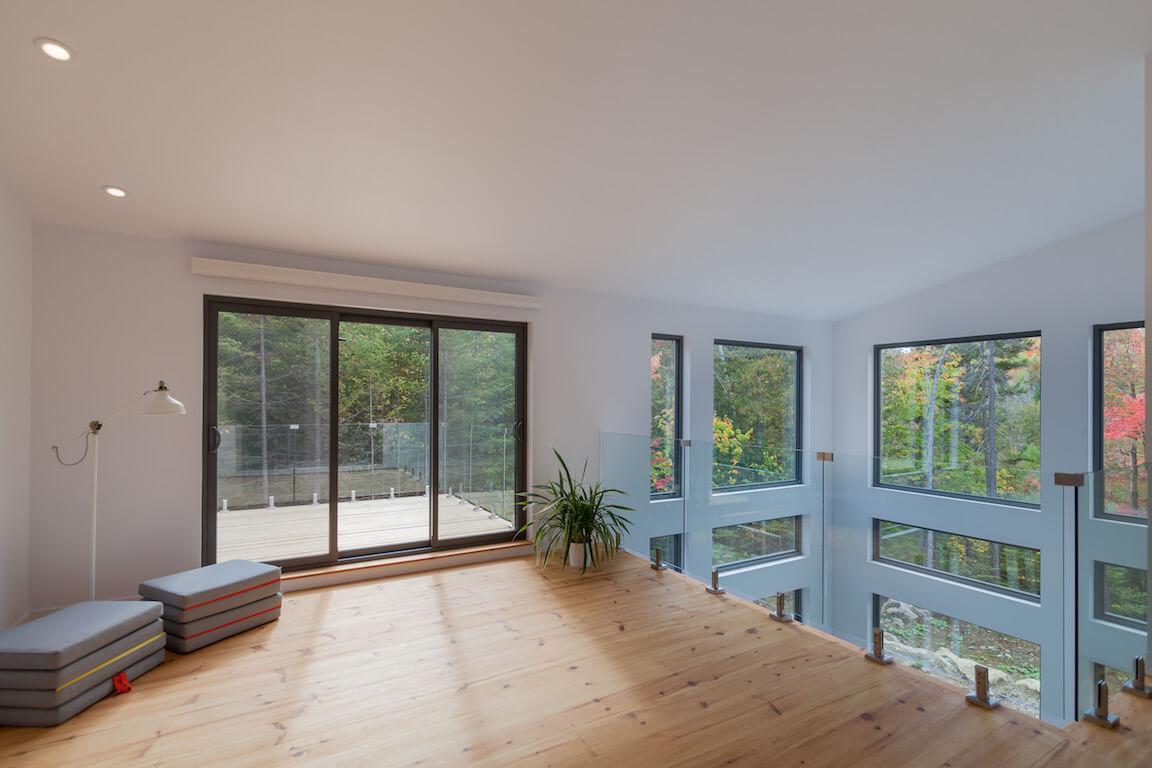 Séjour à aire ouverte à l'étage surplombant le rez-de-chaussée, avec accès au balcon et vue splendide sur la forêt environnante, projet Le Colibri réalisé par Biophile