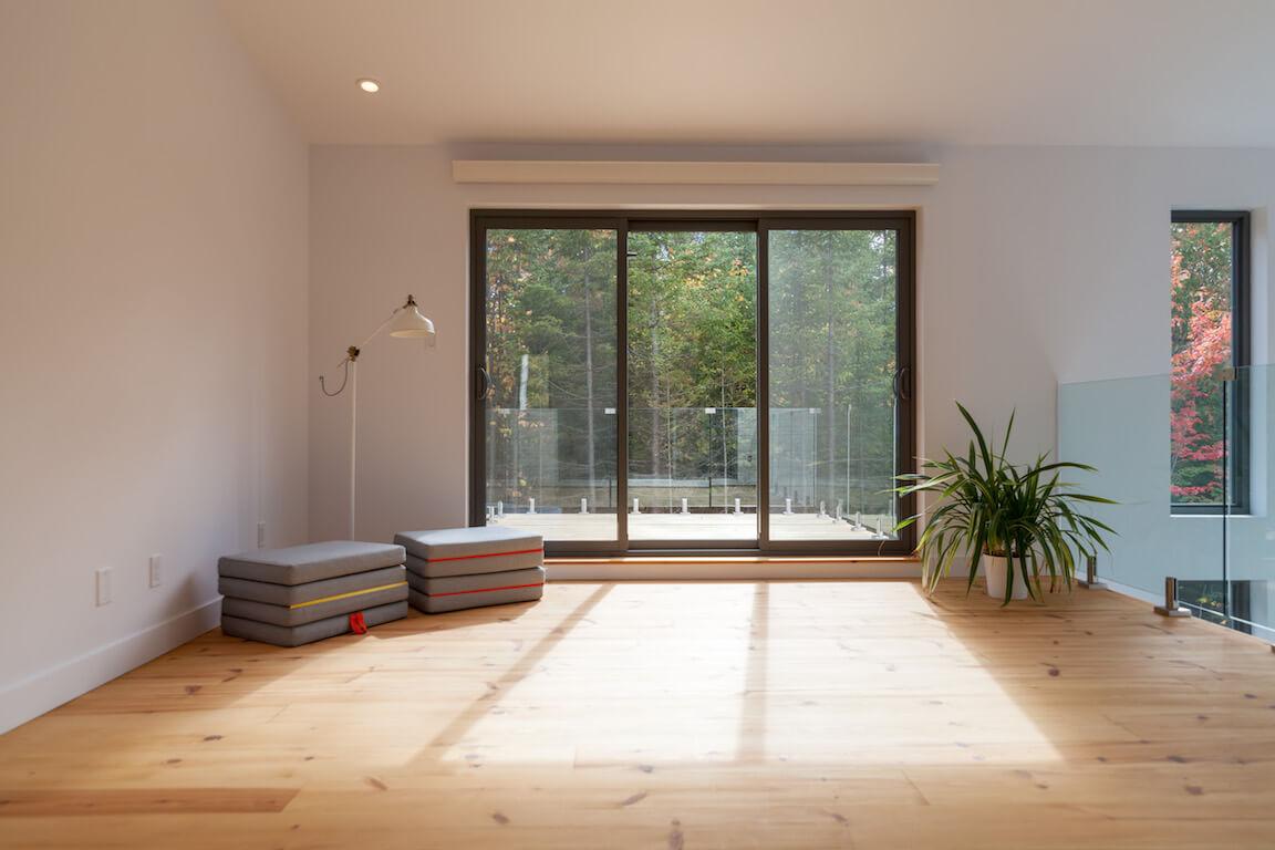 Séjour à aire ouverte à l'étage avec accès au balcon et vue sur la foêt environnante, projet Le Colibri réalisé par Biophile