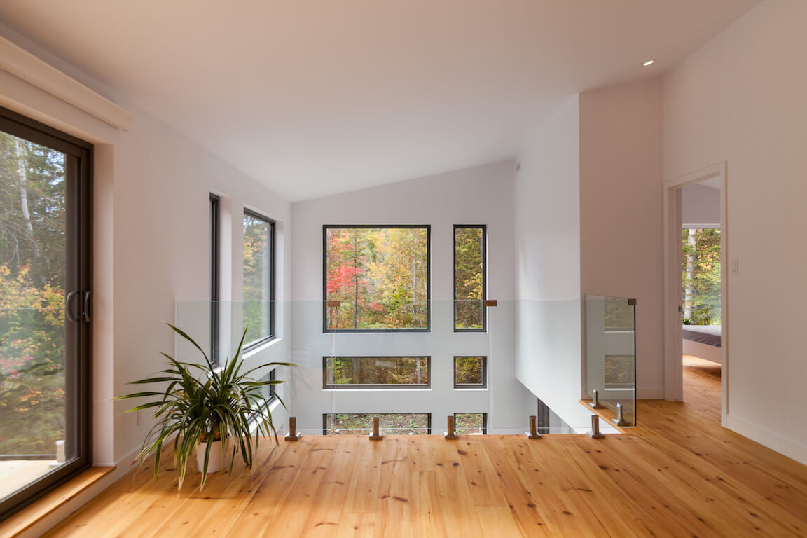 Séjour à aire ouverte à l'étage avec vue sur le rez-de-chaussée, projet Le Colibri réalisé par Biophile
