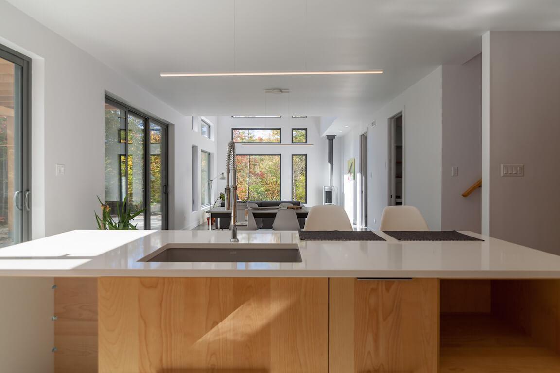 Vue du rez-de-chaussée à aire ouverte avec accès direct à la terrasse, côté sud, projet Le Colibri réalisé par Biophile