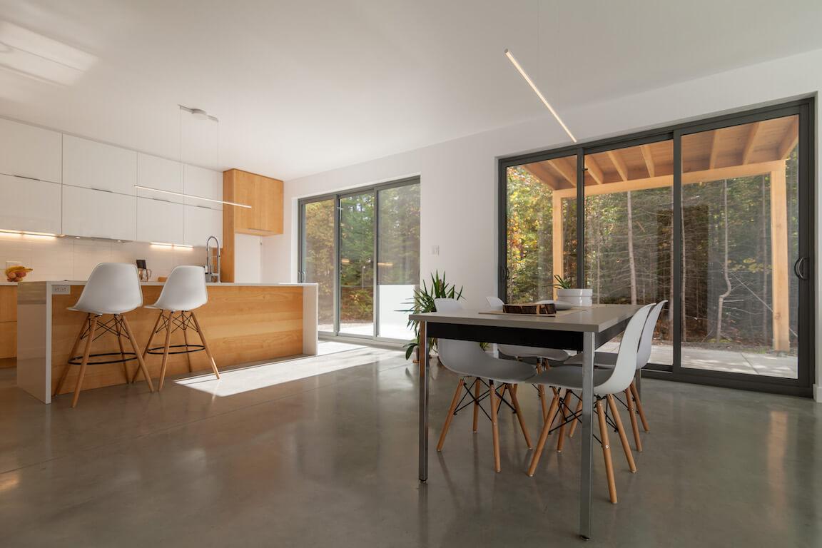 Vue de la cuisine et de la salle à manger à aire ouverte avec accès direct à la terrasse, côté sud, projet Le Colibri réalisé par Biophile