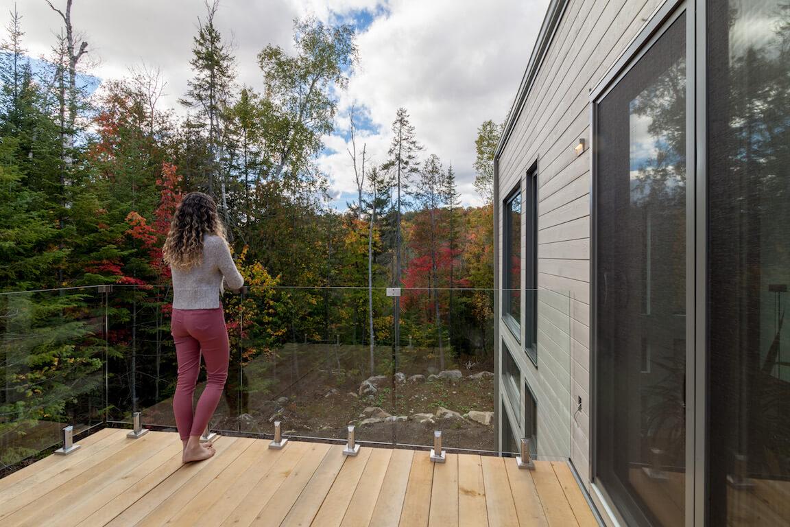Balcon avec garde-corps en verre et vue sur la forêt environnante, projet Le Colibri réalisé par Biophile