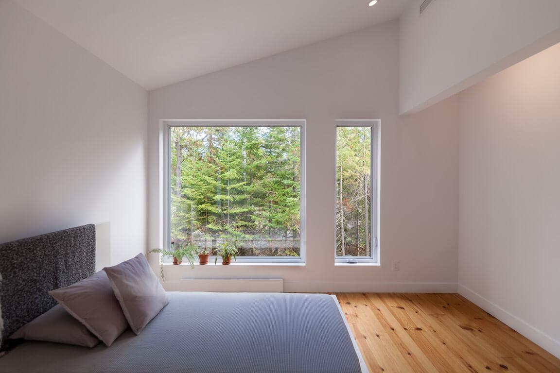 Vue de la chambre à coucher à l'étage avec fenestration du côté est, projet Le Colibri réalisé par Biophile