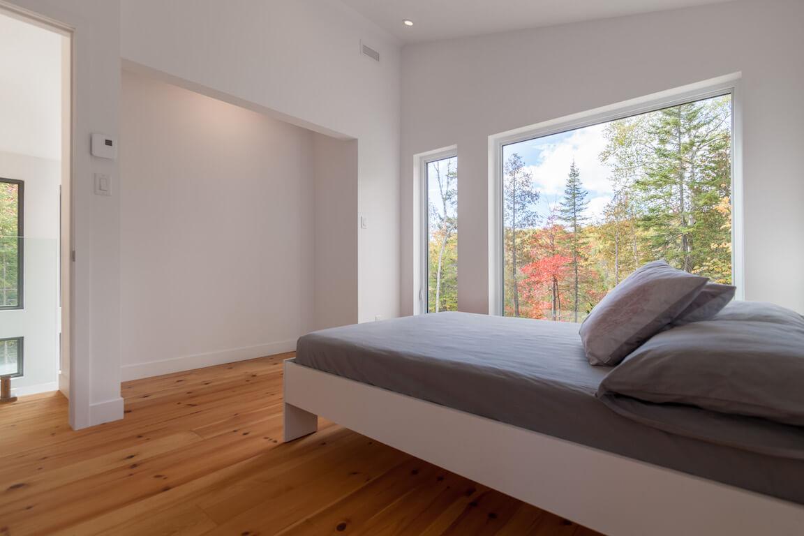 Vue de la chambre à coucher à l'étage avec fenestration du côté ouest, projet Le Colibri réalisé par Biophile