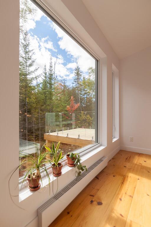 Vue de la chambre à coucher à l'étage avec fenestration du côté sud, projet Le Colibri réalisé par Biophile