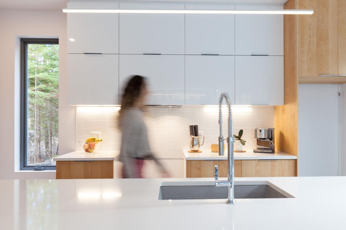Vue de la cuisine à aire ouverte au rez-de-chaussée avec ses armoires pleine hauteur et son ilôt avec comptoir de quartz, projet Le Colibri réalisé par Biophile