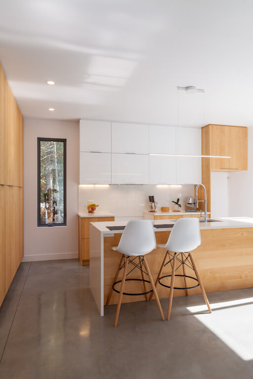 Vue de la cuisine à aire ouverte au rez-de-chaussée avec fenestration du côté est, projet Le Colibri réalisé par Biophile
