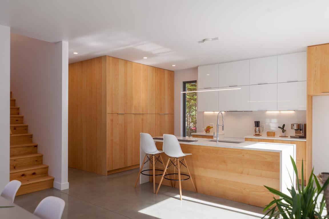 Vue de la cuisine à aire ouverte et de l'escalier au rez-de-chaussée, projet Le Colibri réalisé par Biophile