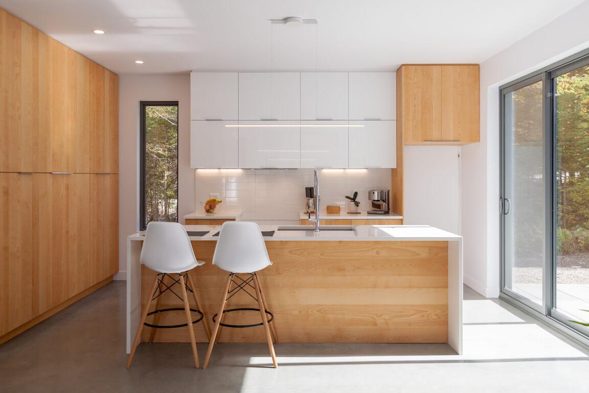Vue de la cuisine à aire ouverte avec un accès direct à la terrasse, côté sud, projet Le Colibri réalisé par Biophile