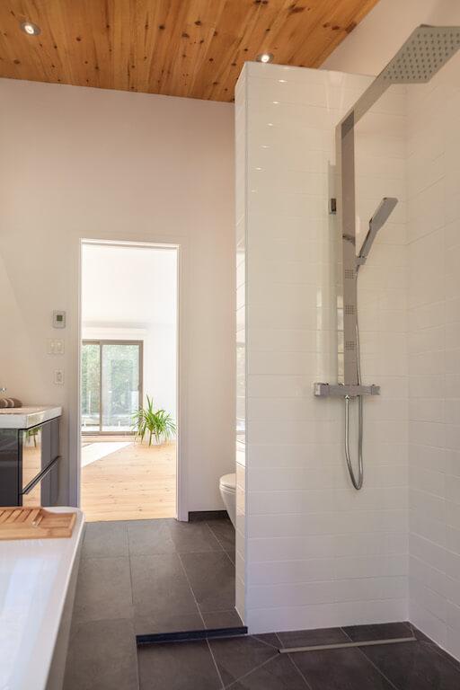 Vue de la salle de bain avec baignoire et douche séparée à l'étage, projet Le Colibri réalisé par Biophile
