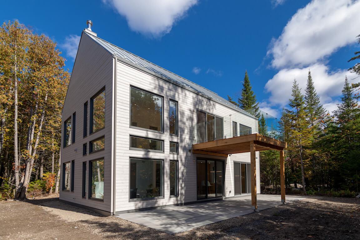 Vue de la façade sud avec terrasse et balcon en pleine nature, projet Le Colibri réalisé par Biophile