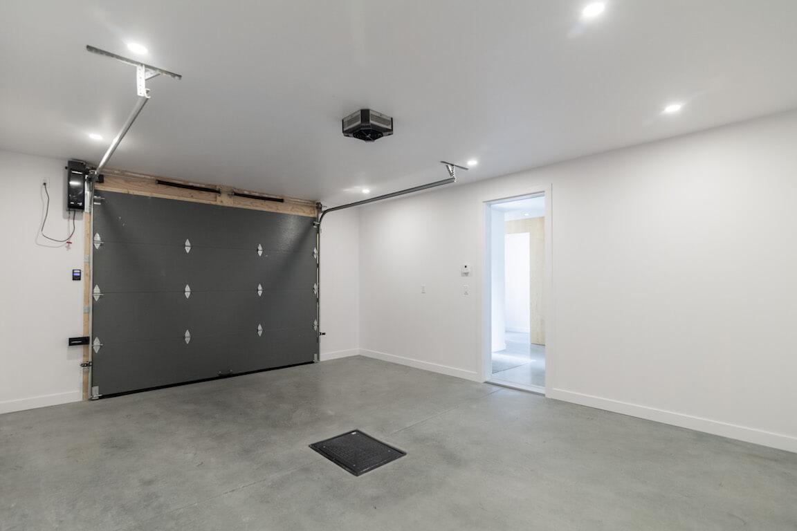 Vue du garage à l'intérieur et de la porte donnant directement accès au hall d'entrée, projet Le Colibri réalisé par Biophile