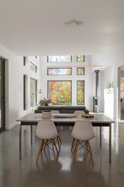 Vue de l'aire ouverte au rez-de-chaussée avec poêle à bois Stuv et fenestration abondante, projet Le Colibri réalisé par Biophile