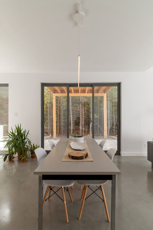 Vue de la salle à manger au rez-de-chaussée donnant un accès direct à la terrasse côté sud en pleine nature, projet Le Colibri réalisé par Biophile