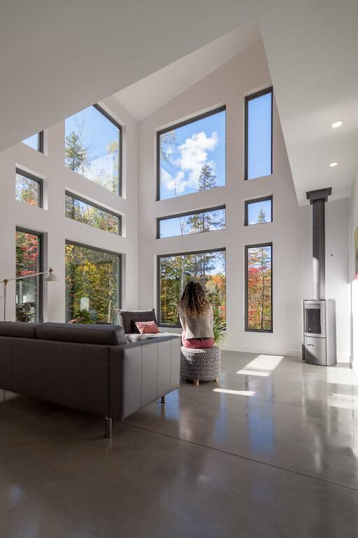Vue du salon à aire ouverte avec poêle à bois Stuv, fenestration abondante et plafond cathédrale, projet Le Colibri réalisé par Biophile