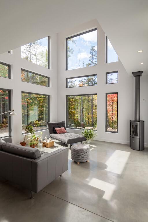 Vue du salon à aire ouverte avec poêle à bois Stuv et fenestration abondante, projet Le Colibri réalisé par Biophile