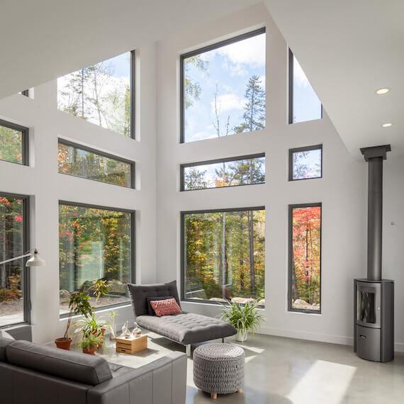 Vue du salon à aire ouverte avec foyer, projet Le Colibri réalisé par Biophile
