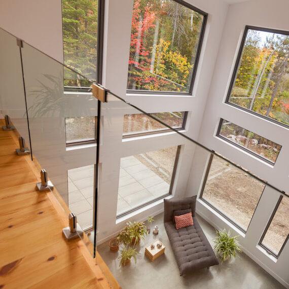 Vue en plongée sur le salon à aire ouverte à partir du séjour à l'étage, projet Le Colibri réalisé par Biophile